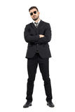 Secret agent or bodyguard with crossed arms looking at camera. Full body length portrait isolated over white studio background stock photography