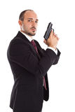Secret agent businessman. A well dressed businessman with a gun posing like a secret agent royalty free stock photos