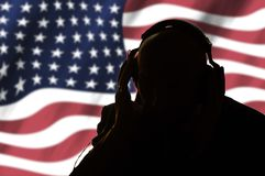 Secret agent in headphones on the background of the American flag royalty free stock photography
