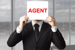 Secret agent hiding face behind sign Royalty Free Stock Photography