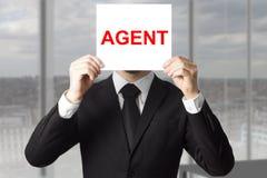 Secret agent hiding face behind sign. Secret agent in black suit hiding face behind sign undercover Royalty Free Stock Photography