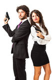 Secret agent and his woman. A businessman and a businesswoman (or maybe a couple of spies or gangster) holding guns over a white background stock photography