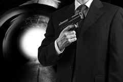 Secret spy agent with a gun. A secret agent holding a gun against a tunnel background with a bright light Stock Photos