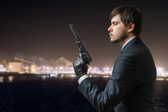 Secret agent holds pistol with silencer in hand at night Royalty Free Stock Images