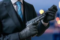 Secret agent holds pistol with silencer in hands at twilight Stock Image