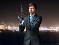Secret agent or killer holds pistol with silencer in hands at night. Royalty Free Stock Image