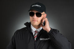 Secret Agent Listening To Earpiece Stock Photography