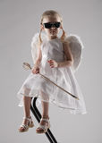 Secret agent of love. Little girl dressed like an angel sitting on bar chair in dark glasses and arrow in hands royalty free stock images