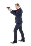 Secret agent man in business suit posing with gun isolated on wh Royalty Free Stock Photo