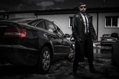 Secret agent man. Cool young stylish man in classic leather coat and sunglasses full-length standing by the luxury automobile at car parking space Stock Photography