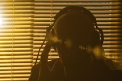 Secret agent overhears a conversation in headphones on the background of the window with blinds, sun glare and toning stock photo