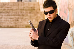 Secret agent ready. Male model performing secret agent with gun royalty free stock photography