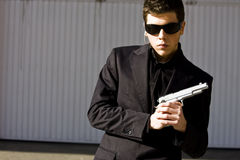 Secret agent ready. Male model performing secret agent with gun royalty free stock image