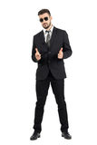 Secret agent with sunglasses aiming hand gun gesture at camera Stock Photo