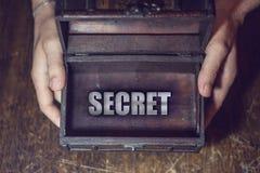 Secret box. Men's hands into the box, which shows a secret Stock Photos