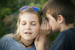 Secret. Boy and girl counting a secret to the ear. instagram effect Stock Image