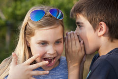 Secret. Boy and girl counting a secret to the ear. instagram effect royalty free stock images