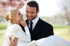 Secret Bridal Whispers. A young 20 something blond women in a silky white wedding dress, held by her 30 something groom, whispers in his ear as they stand under Stock Photos