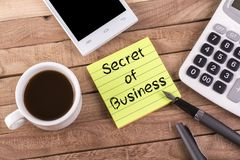 Secret of business on memo. With pen , coffee , mobile and calculator on wooden table Stock Photography