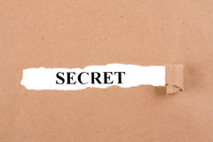 Secret Concept. Word Secret appearing behind torn brown paper stock photography
