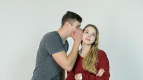Secret de chuchotement de jolie fille dans l'oreille de son ami riant sur le fond blanc - concept d'amitié Images stock