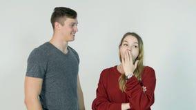 Secret de chuchotement de jolie fille dans l'oreille de son ami riant sur le fond blanc - concept d'amitié Photographie stock libre de droits