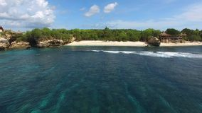 Secret deserted beach and turquoise ocean aerial. Flying over frothy waves of turquoise Indian Ocean to secret deserted beach with white sand surrounded by rocks stock video