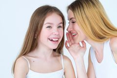 Secret family trust relationship mother whisper. Secret sharing. family trusting relationship. mother whispering something into her daughter ear Royalty Free Stock Photography