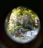 Secret garden. Looking through a hole in a door at a garden Royalty Free Stock Photos