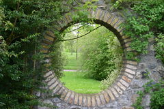 Secret Garden. View through a brick wall into a beautiful secret garden Stock Images
