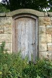 Secret garden door. At the end of a walled garden this very old door always makes me smile as no one has been through it for years but it has been beautifully royalty free stock photography