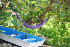 Secret getaway. Remote island hammock with boat parked under it Royalty Free Stock Image