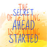 `The secret of getting ahead is getting started` text on yellow paint splash backdrop. VECTOR hand-drawn letters. Orange. And blue words on yellow splash Stock Photo