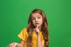 The young teen girl whispering a secret behind her hand over green background. Secret, gossip concept. Young teen girl whispering a secret behind her hand stock image