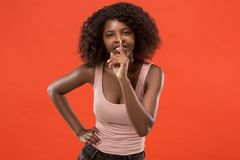 The young woman whispering a secret behind her hand over red background. Secret, gossip concept. Young woman whispering a secret behind her hand. Business woman royalty free stock image