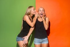 The young woman whispering a secret behind her hand over studio background. Secret, gossip concept. Young women whispering a secret behind her hand. Business stock photography
