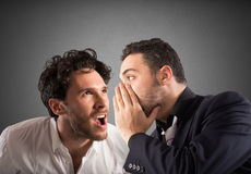 Secret gossip. Man talking the ear of another man royalty free stock images