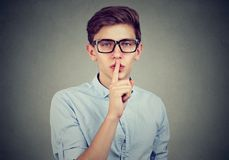 Secret guy. Man saying hush be quiet with finger on lips gesture looking at camera. Isolated on gray wall background Royalty Free Stock Images