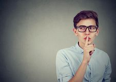 Secret guy. Man saying hush be quiet with finger on lips gesture looking to the side. Isolated on gray wall background Stock Photography