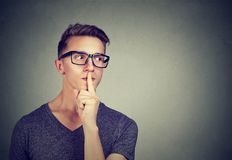 Secret guy. Man saying hush be quiet with finger on lips gesture looking to the side. On gray wall background Royalty Free Stock Images
