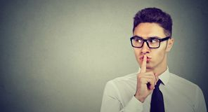 Secret guy. Man saying hush be quiet with finger on lips gesture looking to the side. On gray wall background Stock Image