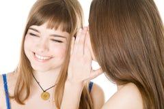 secret heureux d'amies indiquant deux jeunes Photo libre de droits