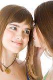 secret heureux d'amies indiquant deux jeunes Photos libres de droits