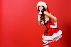 Secret on holidays. Attractive young woman in Santa Claus costume over red background. Christmas Stock Photography