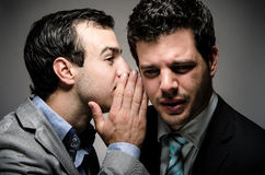 Secret. Image of a men wearing a suit whispering to another men wearing a suit Stock Photos