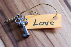 Secret key for love in life. Concept for a happy loving life using an old decorative key and a hand written tag attached by a golden cord stock image