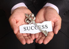 Secret key for success in business. Silver key and success note in busines man hands Royalty Free Stock Images