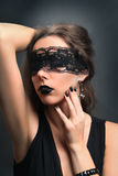 Secret portrait. Young woman with black lace on her eyes Stock Photography
