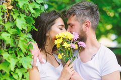 Secret romantic kiss. Love romantic feelings. Moment of intimacy. Couple in love hiding behind bouquet flowers kiss. Couple love romantic date nature stock images