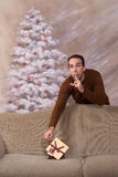 Secret Santa. A secret santa is leaving behind his gift on a sofa and telling the viewer to be quiet Royalty Free Stock Photo